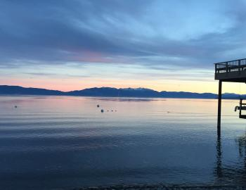Lake Tahoe at sunset with greens and blues in the sky
