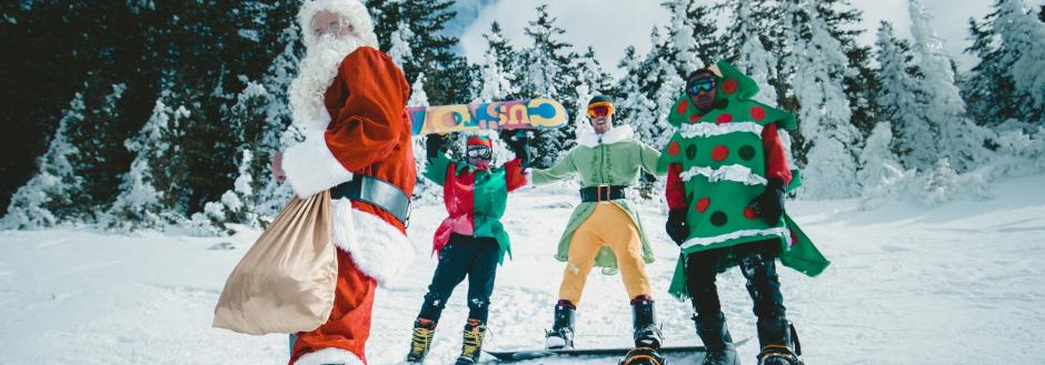 Skiers and snowboarders dressed in holiday attire