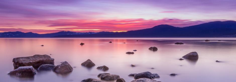 Lake Tahoe at sunset with vibrant pinks and purples in the sky