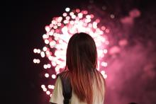 Girl watching a fireworks show as pink fireworks explode in the air