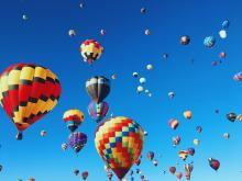 Hot air balloons floating high in the sky at a hot air balloon event